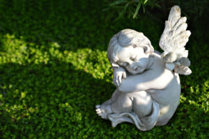 Stone cherub sits in fetal position on grass. Inspiring funeral readings can complement the eulogy and lift hearts and minds.